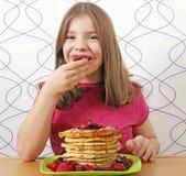 饥饿的小女孩吃薄煎饼 免版税库存照片
