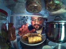 饥饿的年轻人采取板材用从开放冰箱的薄煎饼 免版税库存照片