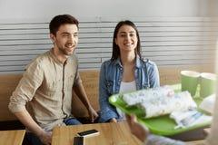饥饿的年轻夫妇在坐在自助食堂的日期,一起花费时间,等待侍者带来与激动的命令 免版税库存照片