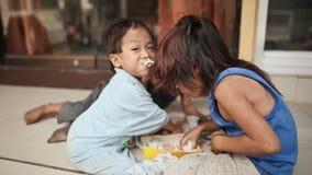 饥饿的无家可归的孩子贪婪吃米遗骸在马尼拉街上的 股票视频