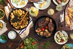 饭桌用烤牛排,菜,土豆,沙拉,锡 免版税库存照片