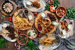 饭桌用虾,鱼烤了,沙拉、不同的快餐和储藏啤酒,顶视图 免版税库存照片