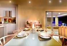 饭桌设置在一个房子里在晚上 免版税库存图片