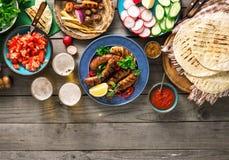 饭桌以烤香肠、玉米粉薄烙饼,啤酒和不同 免版税图库摄影