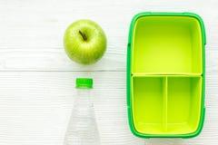 饭盒和水健康食物晚餐的在学校白色桌背景顶视图 免版税库存图片