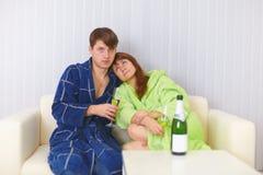 饮料嘶嘶响丈夫坐沙发妻子 库存照片