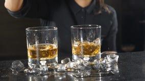 饮料在夜总会 夜生活概念 侍酒者落下的冰块特写镜头射击到与酒精饮料的玻璃里 股票录像