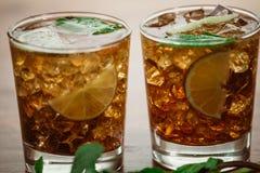 饮料概念-与可乐冰块和石灰的鸡尾酒 免版税库存图片