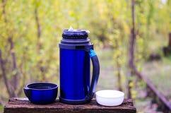 饮料的热水瓶 有两个杯子的热水瓶 使用在自然的一个热水瓶 野营与热水瓶 秋天 免版税库存照片