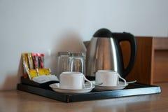 饮料设置了与咖啡杯,水壶,玻璃,茶,咖啡,糖在旅馆客房 库存照片