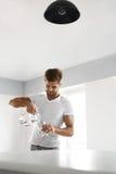 饮料水 关闭人倾吐的水入玻璃 水合作用 库存图片