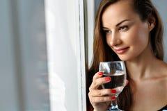 饮料水 微笑的妇女饮用水 饮食 健康生活方式 图库摄影
