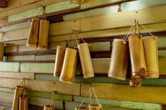 饮用水的竹管 垂悬在木墙壁上 库存照片