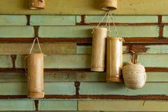 饮用水的竹管 垂悬在木墙壁上 免版税库存照片