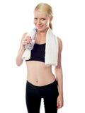 饮用的俏丽的体育运动水穿戴妇女年轻人 免版税图库摄影