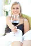 饮用的光芒四射的红葡萄酒妇女 库存图片