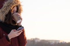 饮用的咖啡和使用智能手机户外在冬天 免版税库存照片