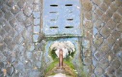 饮用的喷泉水在有鹅卵石的罗马 免版税库存照片