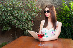 饮用的夫人拿着片剂和在大阳台的酒 图库摄影