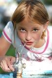 饮用的女孩少许水 免版税库存照片