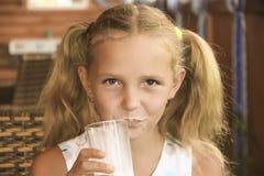 饮用的女孩少许牛奶 免版税图库摄影