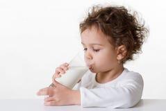 饮用的女孩少许牛奶 免版税库存图片