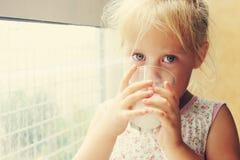 饮用的女孩少许牛奶 图库摄影