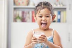 饮用的女孩愉快的小的牛奶 图库摄影