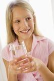 饮用的女孩户内微笑的水年轻人 免版税库存图片
