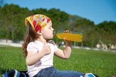 饮用的女孩汁液少许 免版税库存图片