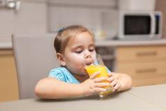 饮用的女孩汁液桔子 免版税图库摄影