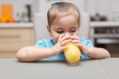 饮用的女孩汁液桔子 免版税库存照片