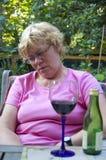 饮用的年长酒妇女 免版税库存照片