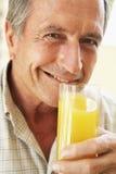 饮用的汁液人橙色高级微笑 库存图片