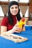 饮用的汁液橙色餐馆妇女年轻人 免版税图库摄影