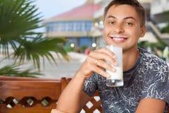 饮用的牛乳气酒人坐的微笑 库存图片