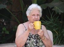 饮用的老茶妇女 库存照片