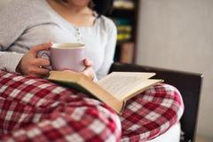 饮用的茶和阅读书 库存图片