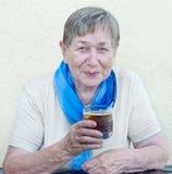 饮用的高级妇女 免版税图库摄影