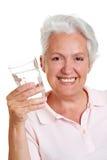 饮用的高级微笑的水妇女 免版税库存图片