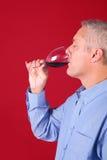 饮用的glas人红葡萄酒 图库摄影