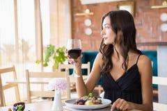 饮用美丽的妇女与膳食的酒 免版税图库摄影