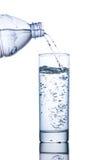饮用水涌入从瓶的一块玻璃 库存图片