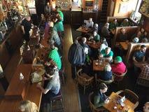 饮者和吃饭的客人在俄勒冈酒吧在圣帕特里克节 免版税库存照片