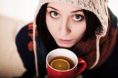 饮者热的咖啡在冬天 一被编织的帽子holdi的一个女孩 库存照片