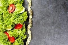 饮食体育运动 菜 测量的磁带,黄瓜,蕃茄,在黑暗的石背景的沙拉 库存图片
