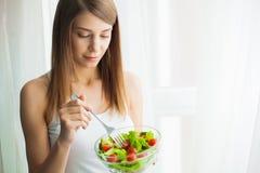 饮食和健康 吃健康食品的年轻女人在锻炼以后 免版税库存图片
