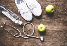 饮食和减重健康关心的与医疗听诊器、健身设备、淡水和绿色苹果在老木backgr 免版税图库摄影