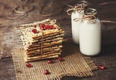 饮食嘎吱咬嚼的薄脆饼干用谷物和牛奶在黑暗的木b 免版税库存图片