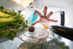 饮食奋斗:充分劫掠从开放冰箱的手一个微小的糖果绿色 库存照片